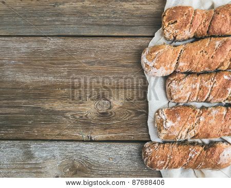 Freshly Baked Rustic  Village Bread (baguettes) Set On Rough Wood Background