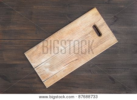 Rustic Square Wooden Cutting Board On A Dark Wooden Desk