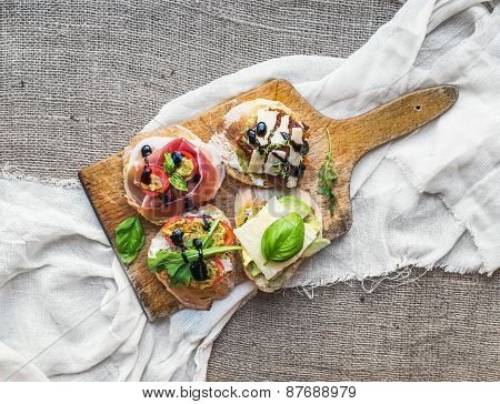 Brusquetta Set On A Rustic Wooden Board Over A Piece Of White Linen Fabric And Sackcloth Surface