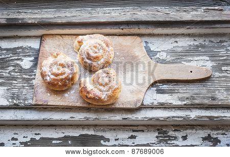 Cinnamon Buns On A Rustic Wooden Board
