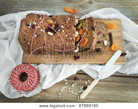 Home-made Whole Grain Christmas Bread With Dried Fruit, Seeds And Nuts On A Wooden Board Over A Piec