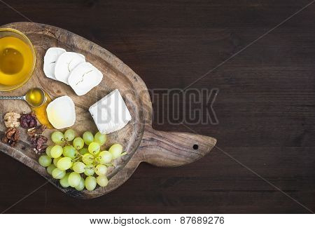 Goat Brie Cheese With Fresh Greapes, Walnuts And Honey On A Rustic Wooden Board Over A Dark Wood Bac