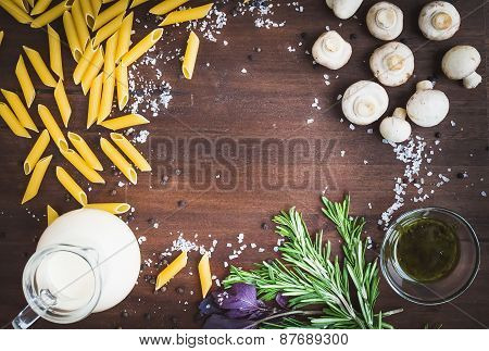 Mushroom Pasta Ingredients: Penne, Mushrooms, A Jug Of Cream, Pesto Sauce, Fresh Herbs And Spices On