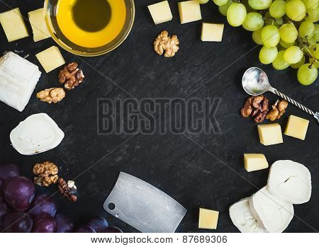 Cheese Selection With Fresh Grapes, Walnuts And Honey On A Dark Stone Background With A Copy Space