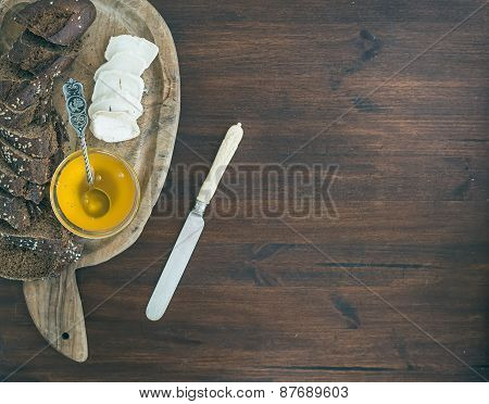 Fresh Dark Baguette Cut In Slices, Goat Brie Cheese And Honey On A Rustic Wooden Board