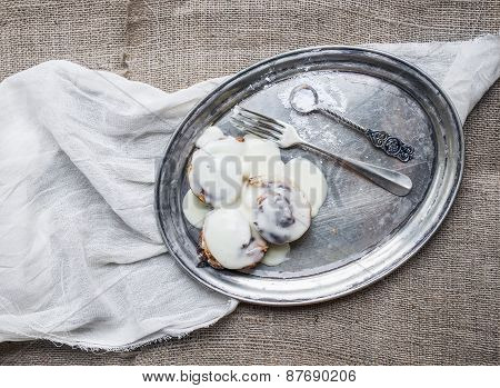 Cinnamon Rolls With Cream-cheese Icing On A Silver Dish Over A Piece Of White Linen Fabric And A Sac
