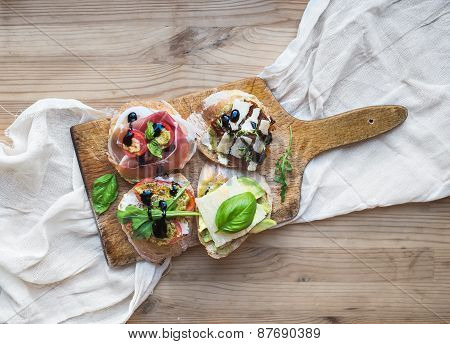 Antipasti Brusquetta Set On A Rustic Wooden Board Over A Linen Kitchen Towel And Wooden Surface