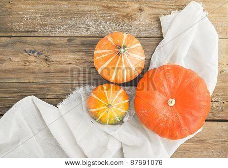 Autumn Pumpkins On A Piece Of Linen Fabric Over A Wooden Board