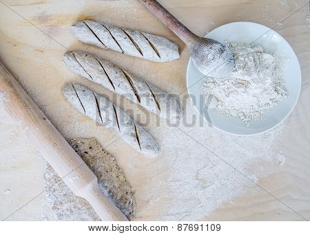 Homemade Baguette Cooking Process: Full Grane Dough, A Rolling Pin, Three Raw Baguettes And Flour On