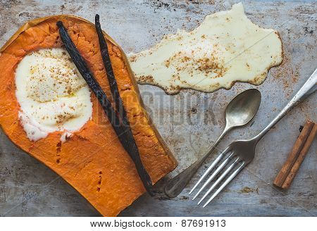 Backed Pumpkin Half With A Scoop Of Vanilla Ice-cream, Vanilla Sticks, Cinnamon, A Fork And A Tea-sp