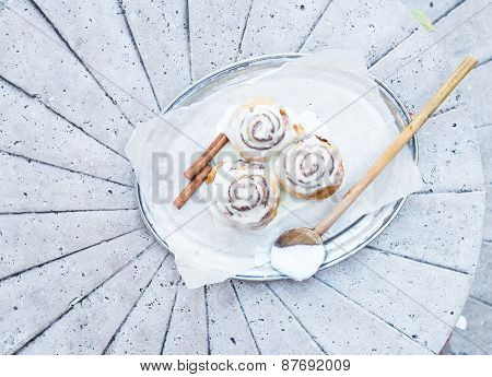 Cinnamon Rolls With Cream-cheese Icing And Cinnamon Sticks On A Silver Dish On A Stone
