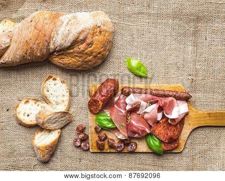 Meat Appetizers Selection And A Loaf Of Rustic Village Bread On A Rough Wood Board Over A Sackcloth