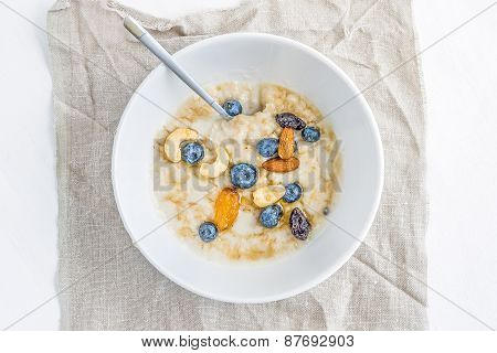 Oat Porridge With Fresh Blueberry, Nuts And Honey In A White Ceramic Bowl On White