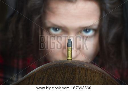 Woman Looking At A Guns Bullet
