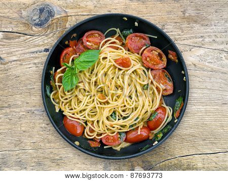 A Pan Of Spaguetti With Tomatoes And Basil