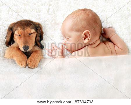 Newborn baby asleep on a blanket.