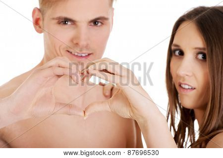 Happy young couple making heart with fingers.