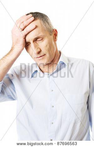 Mature man suffering from headache.