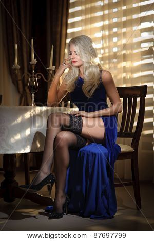 Attractive blonde woman in elegant long dress sitting near a table in a luxurious classic interior.