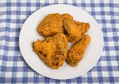 pic of southern fried chicken  - Four pieces of fresh fried chicken on a plate and blue plaid towel - JPG