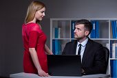 stock photo of inappropriate  - Young seductive secretary working late at office with her boss - JPG
