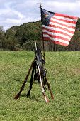 image of civil war flags  - Civil War era muskets stacked next to Union regimental flag