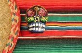stock photo of sombrero  - fiesta mexican poncho serape candy skull in bright colors with sombrero background with copy space - JPG