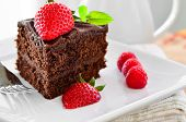 stock photo of chocolate fudge  - Fresh Home Made Sticky Chocolate Fudge Cake With Strawberries And Raspberries and a jug of pouring cream - JPG