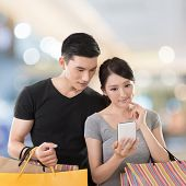foto of mall  - Young Asian couple shopping and looking at cellphone in the mall - JPG