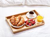 image of bed breakfast  - breakfast in bed with coffee croissants strawberries and juice - JPG