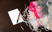 stock photo of garter  - Beautiful pink roses pearl beads and garter lie on a table near the note - JPG