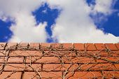 image of wall cloud  - Blue skies and clouds over brick wall - JPG