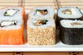 stock photo of soy sauce  - sushi assortment on white plate with soy sauce over bamboo background - JPG