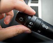 foto of toggle switch  - Closeup shot of man adjusting light control toggle in car - JPG