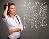 image of anal  - Pretty young woman looking at stock market graphs and symbols - JPG