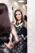 pic of evening gown  - Portrait of a young woman in a dressing room with an evening gown and a statement necklace - JPG