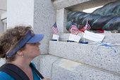 image of veterans  - woman looking at memorial for fallen veteran in Washington DC - JPG
