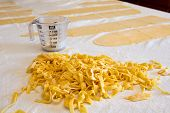 picture of uncut  - Heap of fresh homemade fettuccine pasta prepared with semolina and durum wheat dough on a kitchen counter with sheets of uncut dough and a measuring jug in the background - JPG