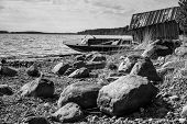 stock photo of old boat  - Old fishing motor boat and barn on lake coast in Karelia - JPG