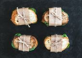 stock photo of paper craft  - Chicken and spinach sandwiches wrapped in craft paper over a dark stone background - JPG