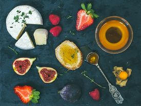 pic of fresh slice bread  - Cheese fresh strawberries figs raspberries ground cherry thyme a slice of bread and a small bawl of honey with a tea - JPG