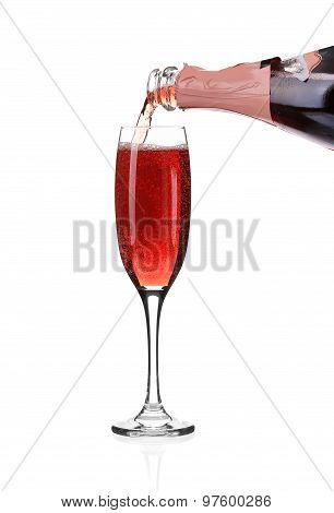 Red champagne pouring in a glass.