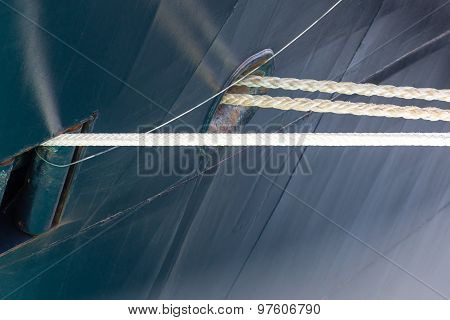 White Ropes Into Blue Ship Hull