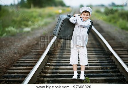 boy with suitcase on railroad