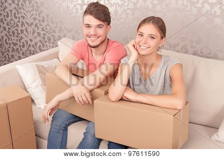 Cheerful couple holding boxes