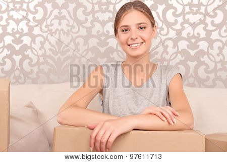 Cheerful young wife holding box