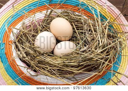 Three Chicken Eggs In A Nest Of Old Hats And Hay