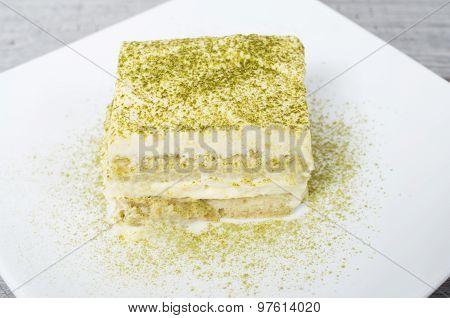 Tiramisu with green tea powder on wooden background