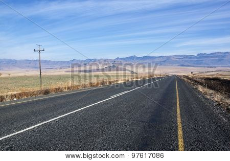 Straight Asphalt Road With Mountains In Background