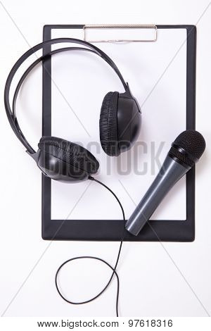 Microphone, Headphones And Clipboard With Blank Paper
